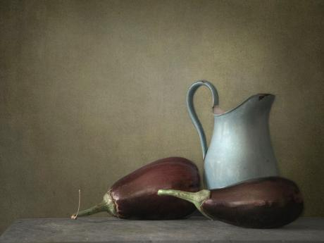 A photograph of two eggplants and a white pitcher on a table