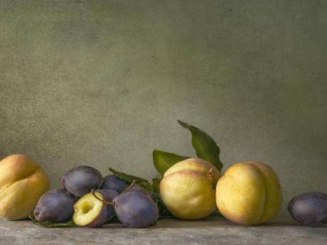 A photograph of several white peaches and plums against a gray backdrop. One of the plums is cut in half and pitted.