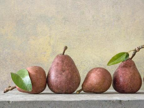 A photograph of five red pears on a table
