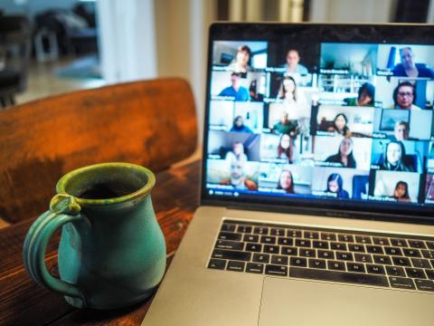 A mug next to a laptop with a screen showing a video conference